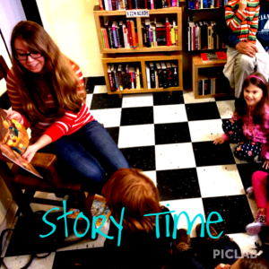 Our story time reader reads to kids sitting on our checkerboard floor.