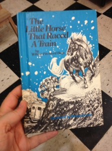 A person's hand holds an older blue book with a black and white drawing of a horse racing a train in the snow.