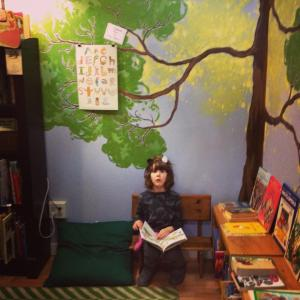 little girl wearing cat ears sitting on a low bench reading a book in the kid's nook.