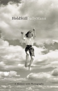 book cover shows a black and white photograph of clouds with a image of girl in 50s style shorts & shirt jumping in the air.